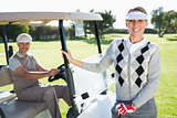 Happy golfing couple smiling at camera with their buggy