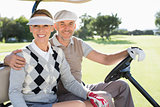 Happy golfing couple driving in their buggy smiling at camera