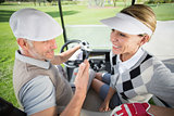 Golfing couple smiling at each other in their golf buggy