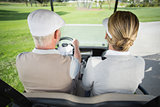 Golfing couple driving in their golf buggy