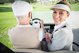 Golfing couple driving in their golf buggy with woman smiling at camera