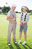 Golfing couple smiling at each other holding clubs