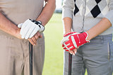 Golfing couple standing and holding clubs