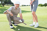 Golfing couple on the putting green with man smiling at camera