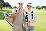 Golfing couple smiling at camera on the putting green