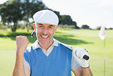 Happy golfer cheering at camera on putting green