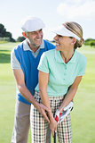 Golfing couple putting ball together smiling at camera each other