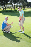 Man coaching his partner on the putting green