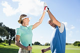 Golfing couple high fiving on the golf course