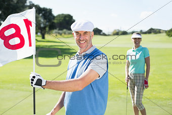 Happy golfer holding eighteenth hole flag with partner behind him