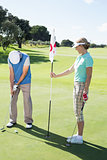 Lady golfer holding eighteenth hole flag for partner putting ball