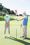 Golfer holding eighteenth hole flag for partner putting ball