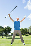 Excited golfer jumping up and smiling at camera