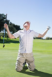 Kneeling golfer cheering on putting green