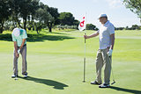 Golfer holding eighteenth hole flag for friend putting ball