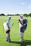 Golfer friends smiling at camera holding their golf bags