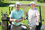 Golfing friends standing beside their buggy smiling at camera