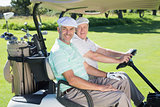 Golfing friends smiling at camera in their golf buggy