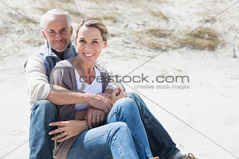 Attractive couple smiling at each other on the beach
