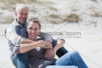 Attractive couple smiling at camera on the beach