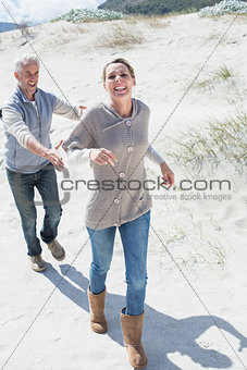 Attractive couple playing chasing on the beach
