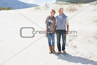 Attractive couple standing holding hands on the beach