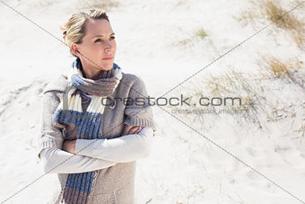 Attractive blonde standing on the beach in woolen scarf