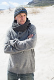 Attractive man shivering on the beach in hat and scarf