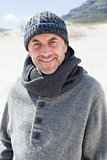 Attractive man smiling at camera on the beach in hat and scarf