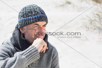 Attractive man smiling on the beach in hat and scarf