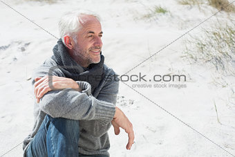 Attractive man smiling on the beach in scarf