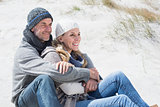 Attractive couple smiling on the beach in warm clothing