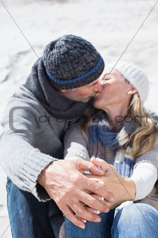 Attractive couple kissing on the beach in warm clothing