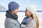 Attractive couple smiling at each other on the beach in warm clothing