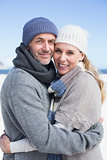 Attractive couple smiling at camera on the beach in warm clothing