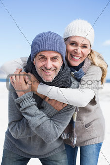 Attractive couple hugging and smiling at camera on the beach in warm clothing