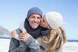 Attractive couple hugging on the beach in warm clothing