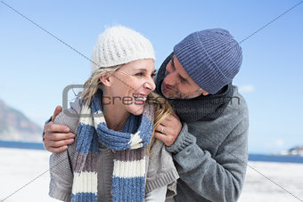 Attractive couple embracing on the beach in warm clothing