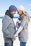 Attractive couple standing on the beach in warm clothing