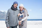 Smiling couple standing on the beach in warm clothing