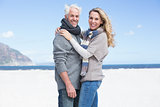 Smiling couple looking at camera on the beach in warm clothing