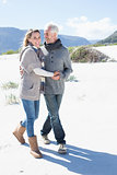 Smiling couple strolling on the beach in warm clothing