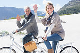 Carefree couple going on a bike ride on the beach waving at camera