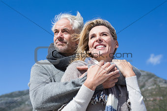 Carefree couple hugging in warm clothing