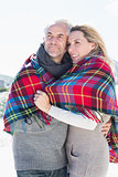 Happy couple wrapped up in blanket standing on the beach