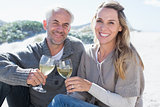 Couple enjoying white wine on picnic at the beach smiling at camera