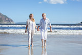 Happy couple walking barefoot on the beach