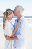 Man kissing his partner on the forehead at the beach