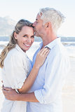 Man kissing his smiling partner on the forehead at the beach