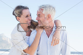 Attractive married couple hugging at the beach